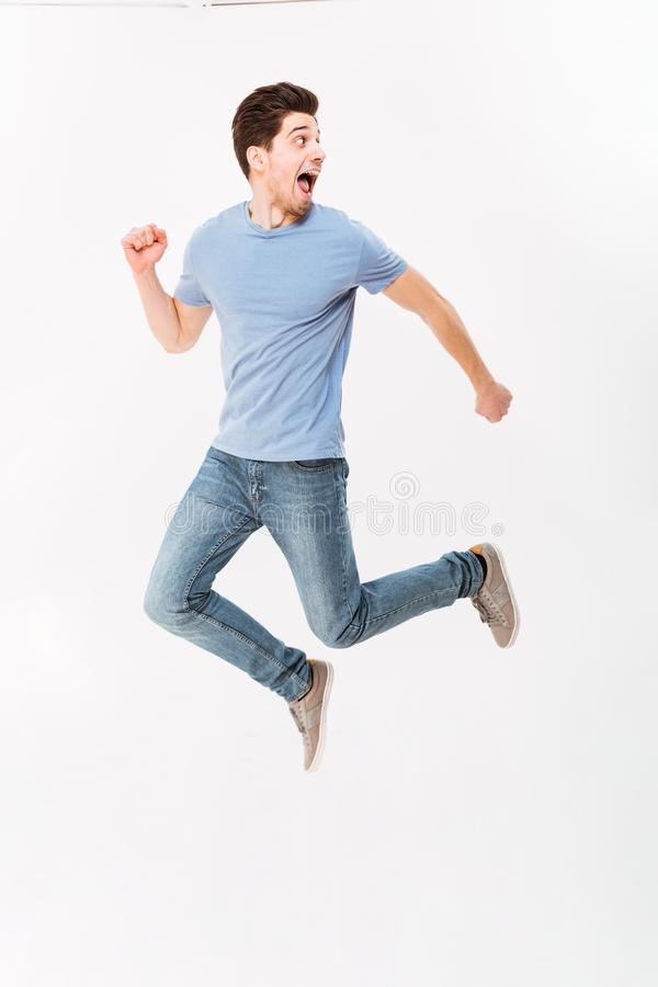 Full-length photo of uptight scared man 30s in casual t-shirt an. D jeans running away in studio isolated over white background stock photo