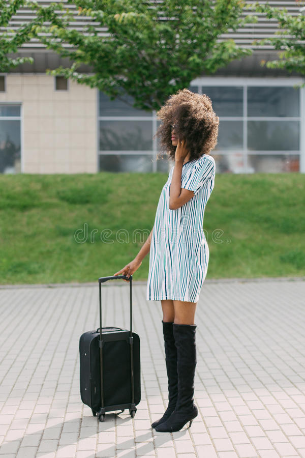Full-length photo of the well-dressed afro-american woman holding the luggage while talking via the mobile phone. Full-length photo of the well-dressed afro stock images