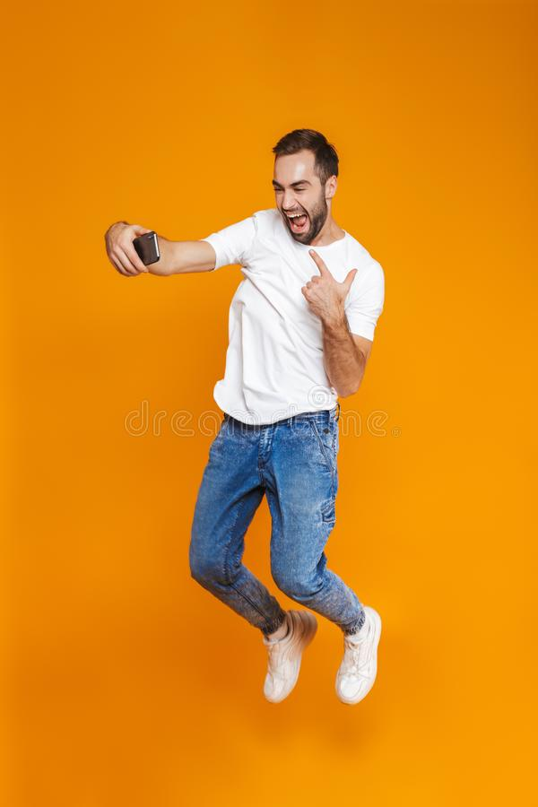 Full length photo of young guy 30s in casual wear laughing and taking selfie on cell phone, isolated over yellow background royalty free stock image