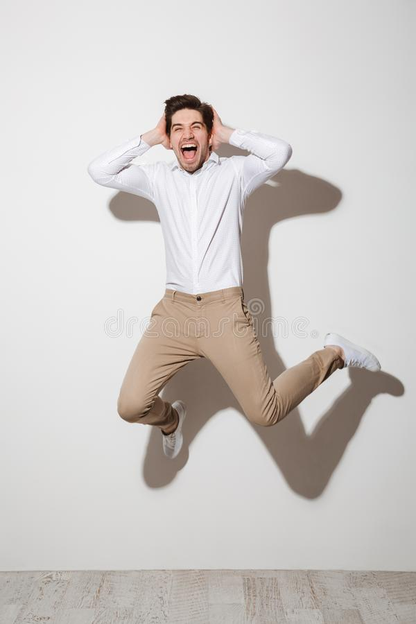 Full length picture of joyful guy in shirt and trousers jumping. Grabbing head with scream isolated over white background with shadow royalty free stock photo