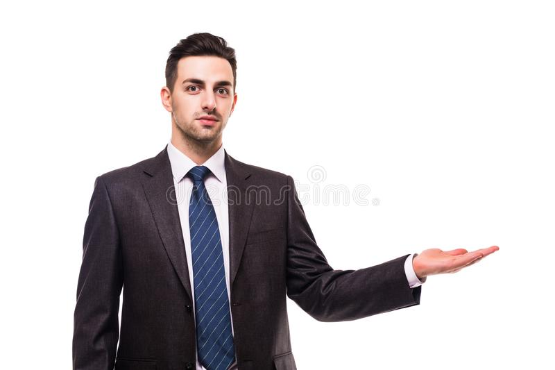 Full length picture of a young business man presenting something in the back with one hand in his pocket while looking at the came royalty free stock images