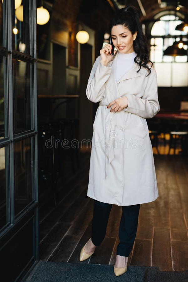 Full length portait of elegant businesswoman wearing white overcoat, stylish shoes and black trousers standing in cafe calling he royalty free stock images