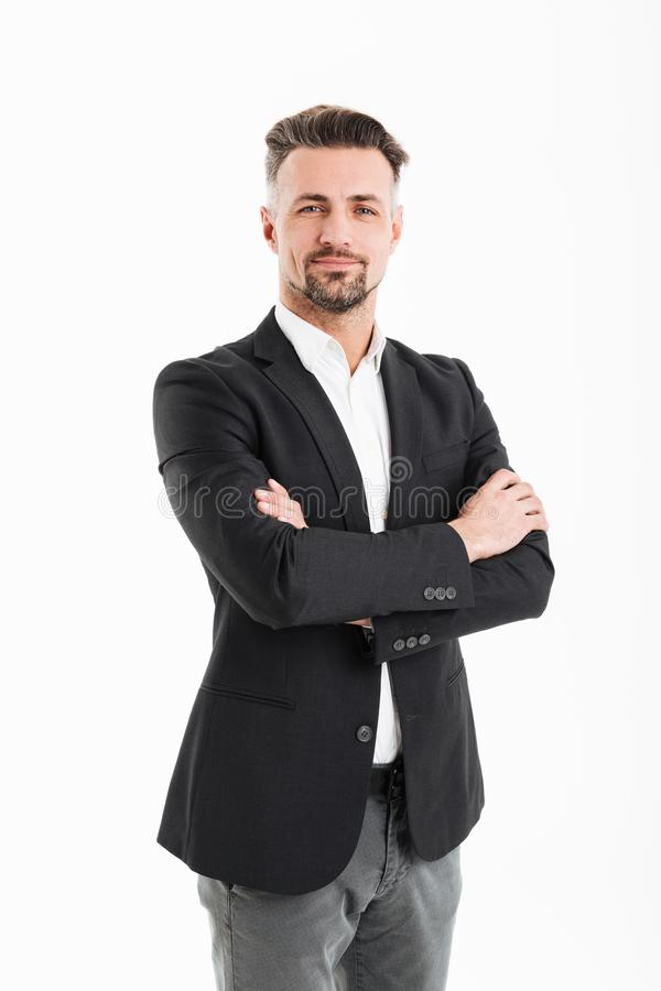 Full-length portrait of adult man 30s in businesslike suit posing on camera with hands crossed, isolated over white background stock photos