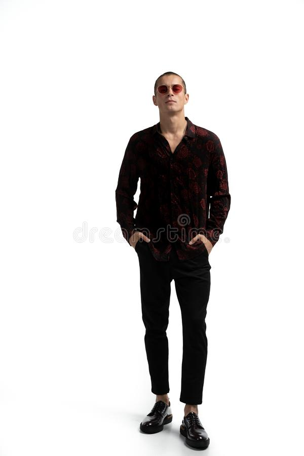 Full length portrait of amazing attractive man in stylish trendy clothes, wearing red sunglasses, holding hands in stock photos