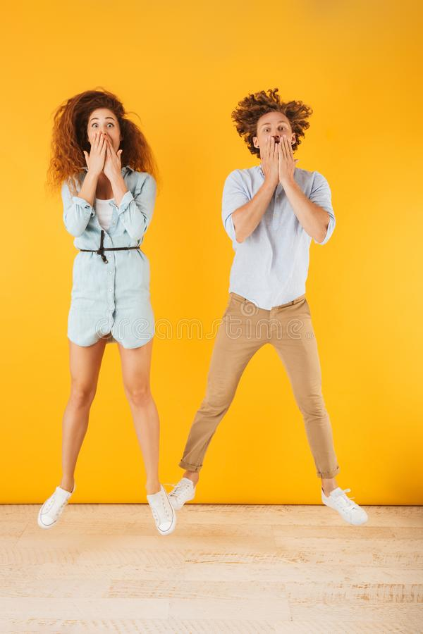 Full length portrait of amusing pleased couple man and woman 20s covering mouth with hands together, isolated over yellow. Full length portrait of amusing stock photography