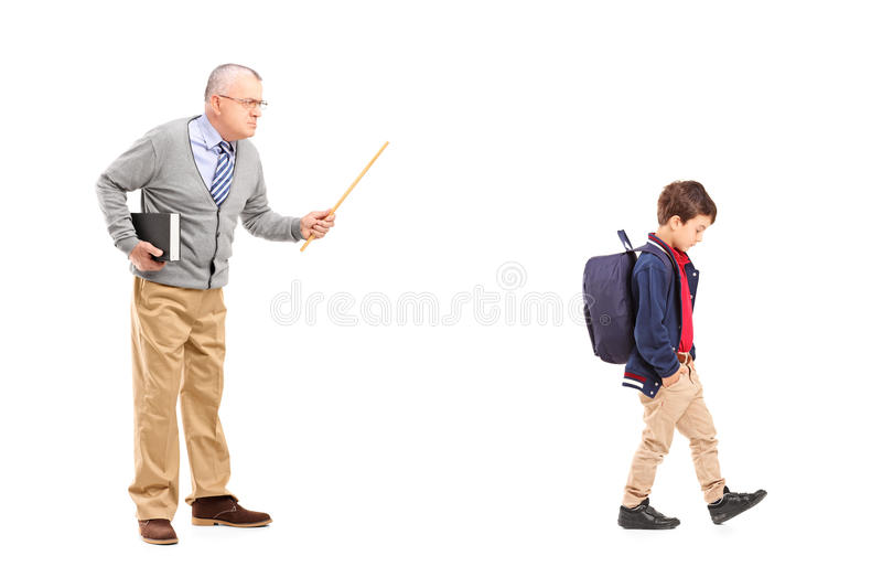 Full length portrait of an angry teacher shouting at a little sc stock photo