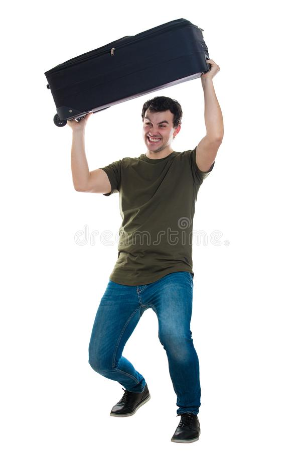 Heavy luggage. Full length portrait of angry young man traveler lifting his suitcase over head trying to throw it. Guy having a heavy luggage isolated over white stock photo