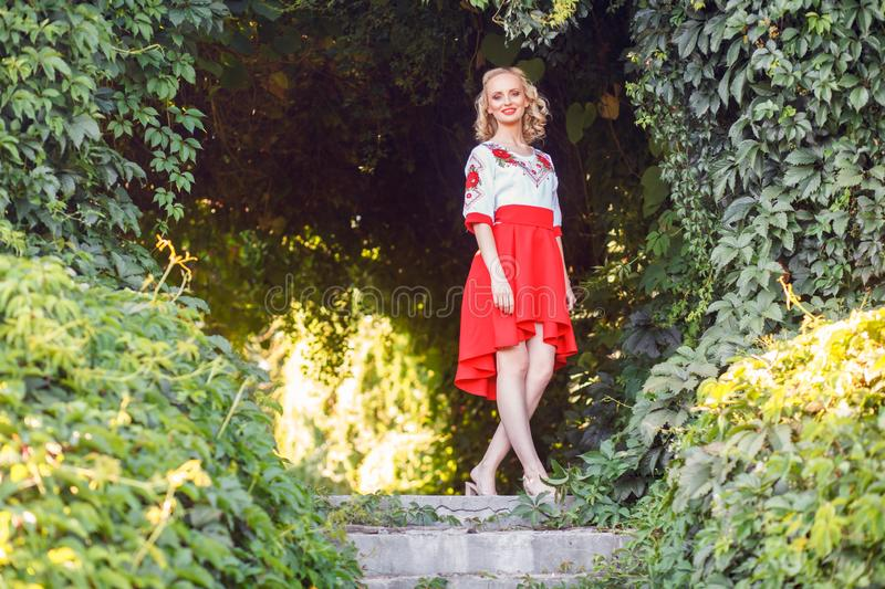 Full length portrait of attractive blonde young woman in stylish dress posing near floral arch in garden. standing and looking at royalty free stock images