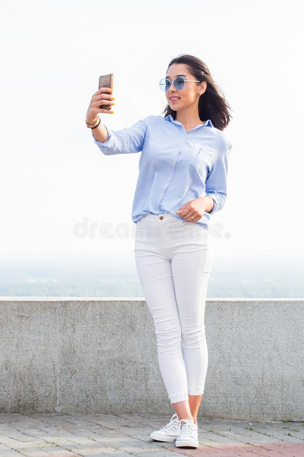 Full length portrait of attractive brunette woman doing selfie on smartphone outdoor. Street royalty free stock photo