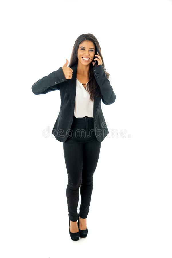 Full length portrait of Attractive latin corporate latin woman on her mobile excited and making thumb up sign in Creative success stock image
