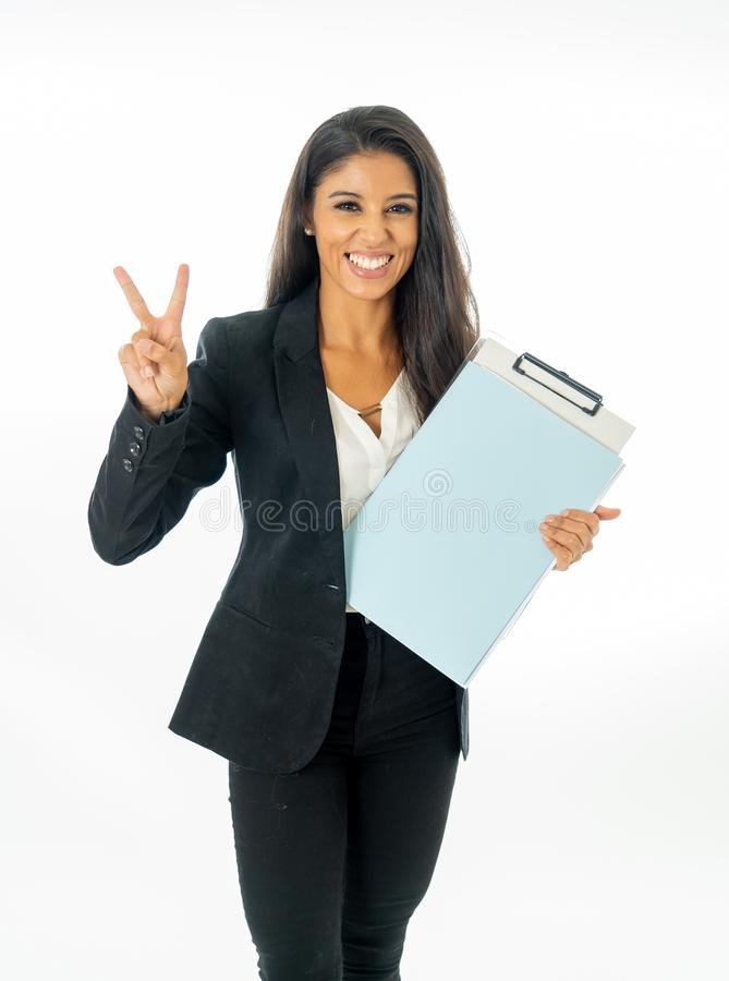 Full length portrait of Attractive latin corporate latin woman looking excited and holding folder and paperwork in Creative royalty free stock image