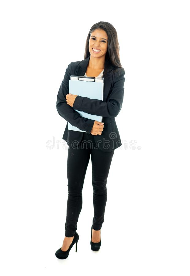 Full length portrait of Attractive latin corporate latin woman looking excited and holding folder and paperwork in Creative stock photo