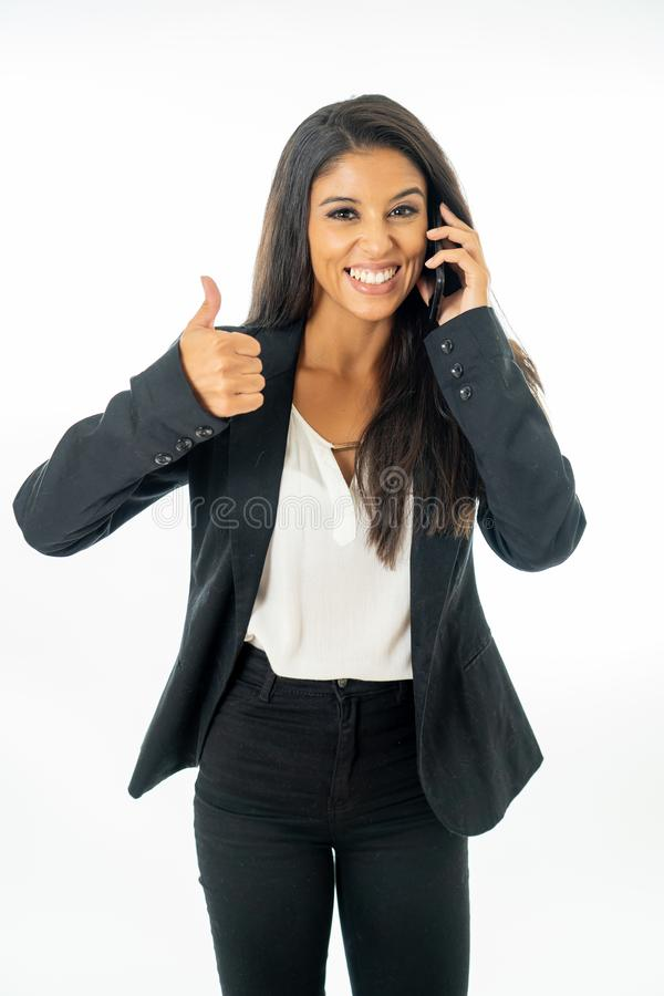 Full length portrait of Attractive latin corporate latin woman talking on smart phone and making thumb up sign in Creative success royalty free stock photography