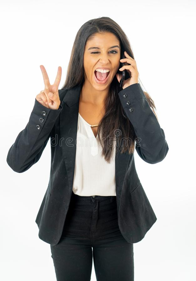 Full length portrait of Attractive latin corporate latin woman talking on smart phone and making victory sign in Creative success royalty free stock image