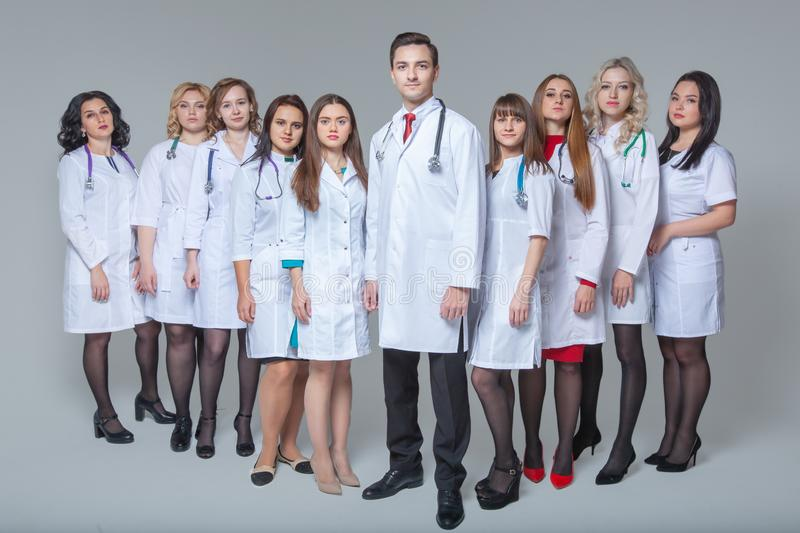 Full length portrait of an attractive male doctor staying at the head of group of doctors royalty free stock photo