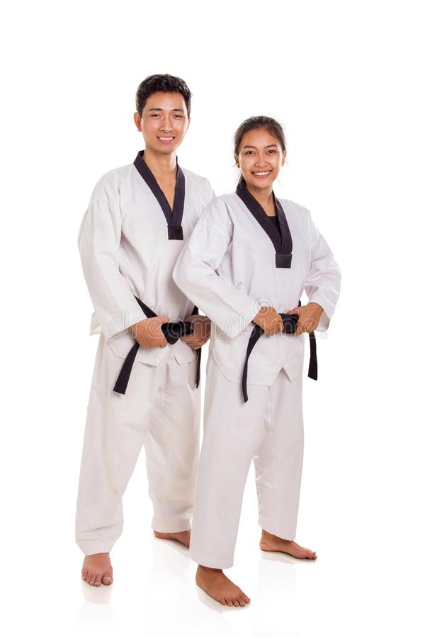 Martial arts couple standing pose and smile, studio background royalty free stock images