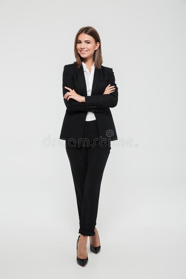 Full length portrait of an attractive smiling businesswoman. In suit standing with arms folded and looking at camera isolated over white background royalty free stock image