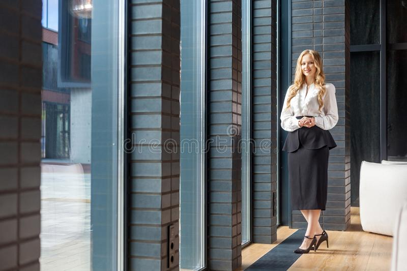 Full length portrait of attractive successful businesswoman with long blond hair in office style clothes. Standing near windows of modern business center stock photo