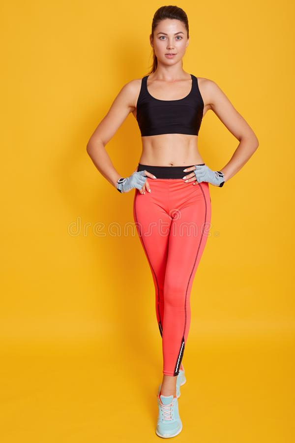 Full length portrait of attractive woman, image of body of fit female wears sports bra and leggins, shows slim belly and press,. On yellow wall. Diet, fitness stock photos