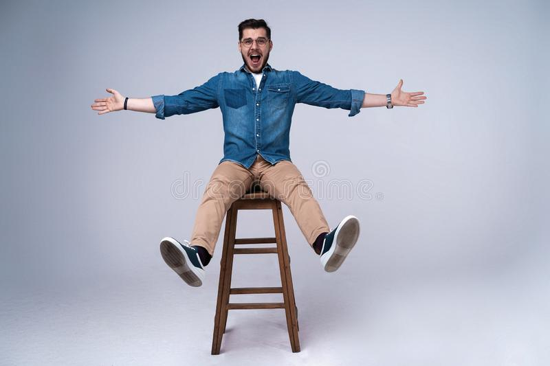 Full length portrait of an attractive young man in jeans shirt sitting on the chair over grey background. stock image