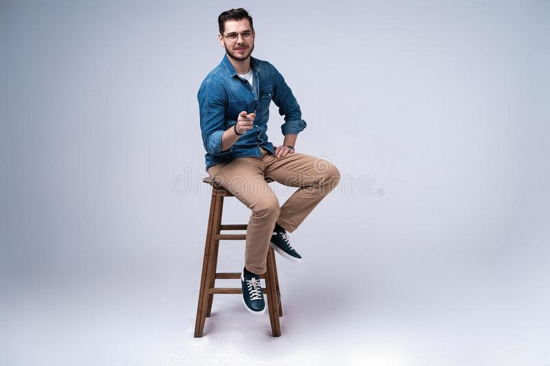 Full length portrait of an attractive young man in jeans shirt sitting on the chair over grey background. stock photography