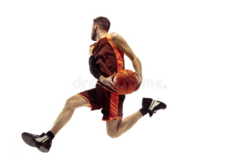 Full length portrait of a basketball player with ball. Isolated on white background. Advertising concept. Fit caucasian athlete jumping at studio. Motion royalty free stock image