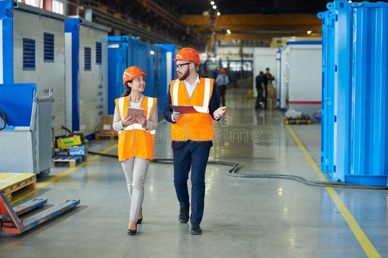 Investor Touring Modern Factory. Full length portrait of bearded businessman wearing hardhat talking to smiling female factory worker while discussing production stock photos