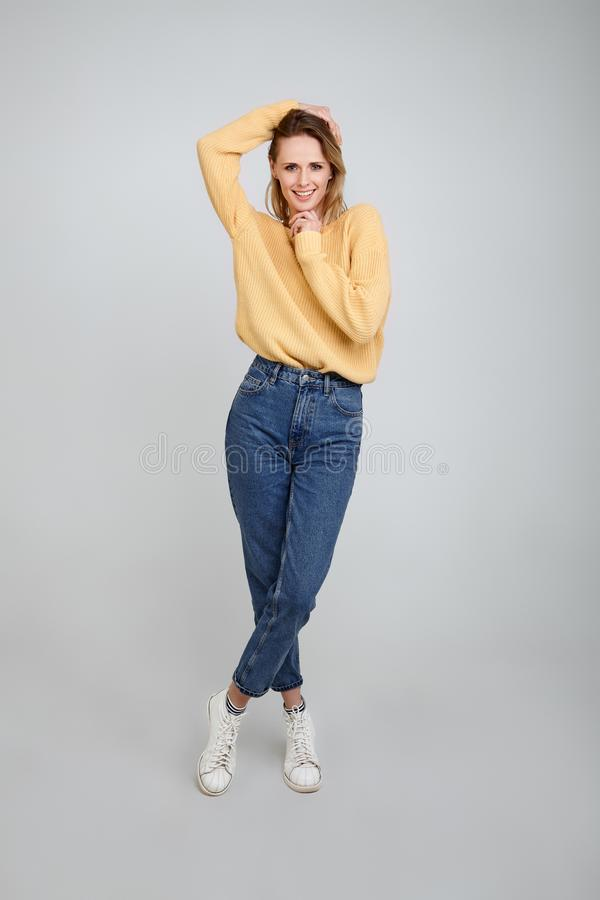 A full-length portrait of a beautiful blonde, dressed in stylish clothes. With one hand he holds his hair and the other hand holds royalty free stock photos