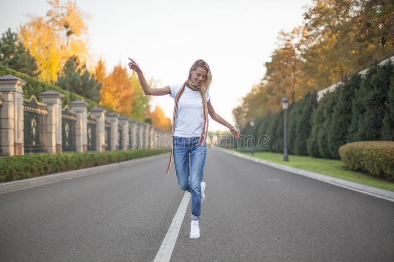 A full-length portrait of a beautiful blonde who dances in the middle of a road in a large park. Hands raised to the side stock image