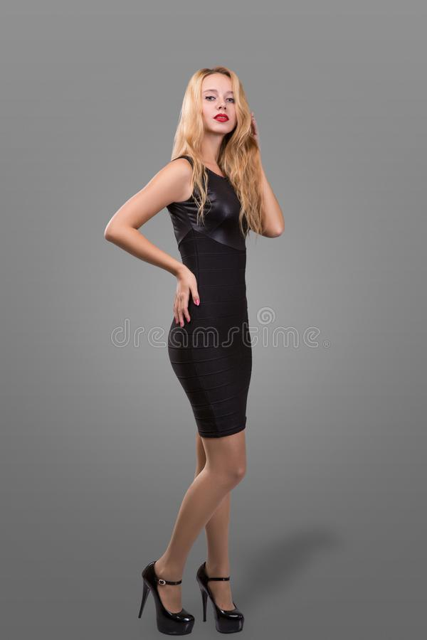 Full Length Portrait of a Beautiful Blonde Woman in Little Black Fashion Dress. Gray Background. royalty free stock photography