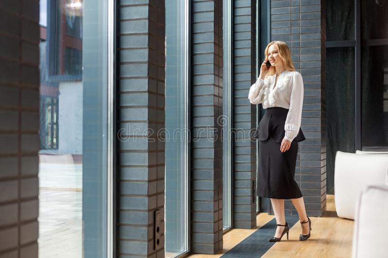 Full length portrait of beautiful elegant businesslady looking out window of business center and talking on cellphone. indoors. Full length portrait of beautiful royalty free stock photography