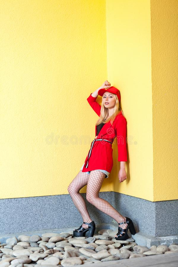 Full length portrait of beautiful fashion blonde young hipster woman in red blouse and cap posing near yellow wall royalty free stock photography