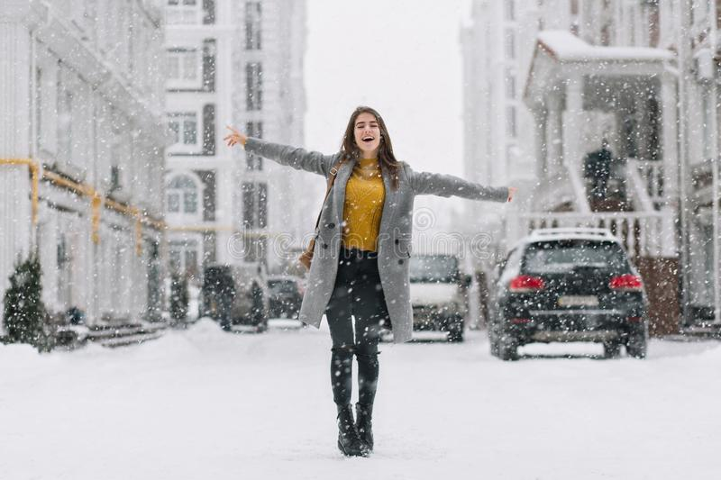 Full-length portrait of beautiful female model wears gray coat in cold winter day. Wonderful caucasian girl in yellow royalty free stock images