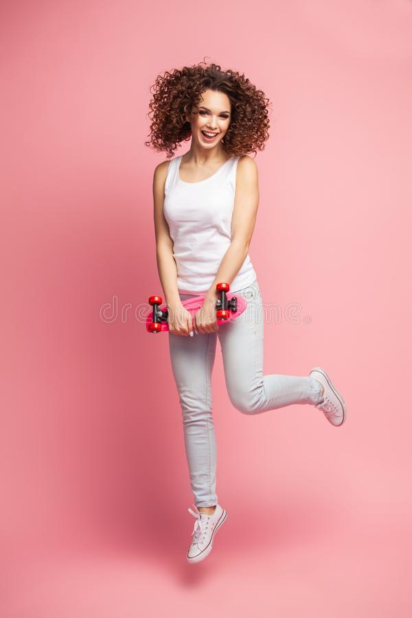 Full length portrait of a beautiful happy woman in summer clothes posing and looking away while jumping and holding royalty free stock image