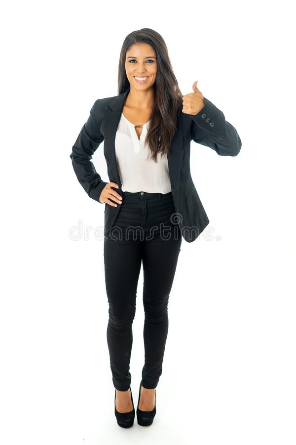 Full length portrait of a beautiful latin businesswoman smiling and making thumbs up sign standing isolated on a white background stock image