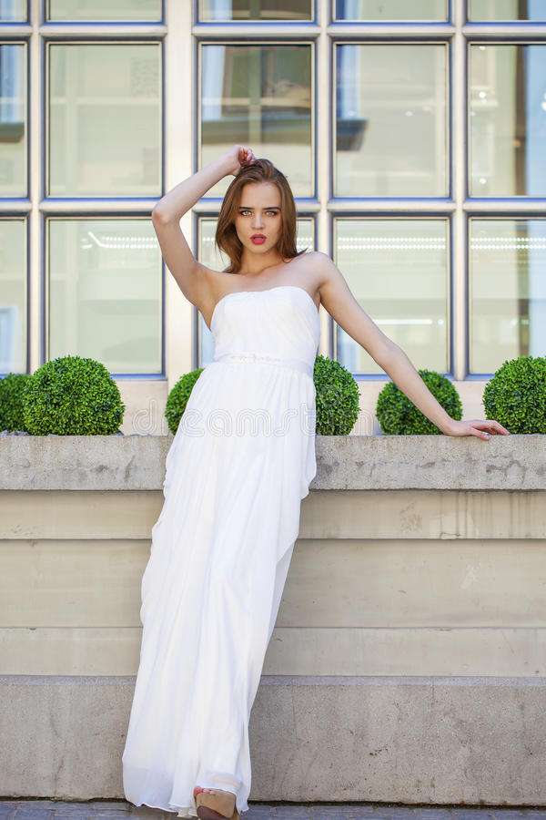 Full length portrait of beautiful model woman with long legs wearing white dress stock image