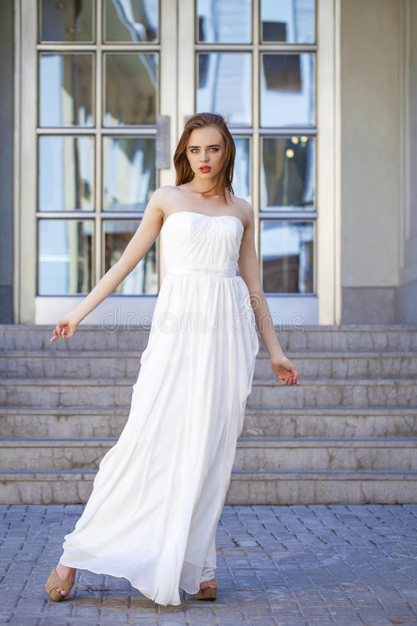 Full length portrait of beautiful model woman with long legs wearing white dress royalty free stock photo