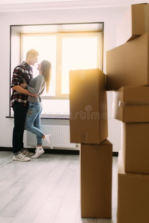 Full length portrait of beautiful young couple hugging and smiling while standing among moving cardboard boxes royalty free stock photos