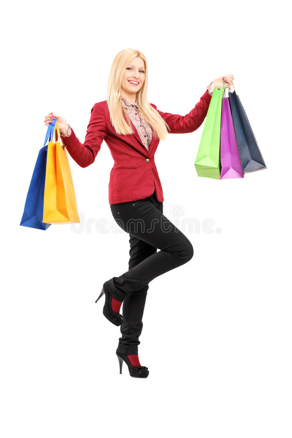 Full length portrait of a blond smiling woman holding shopping b royalty free stock photos