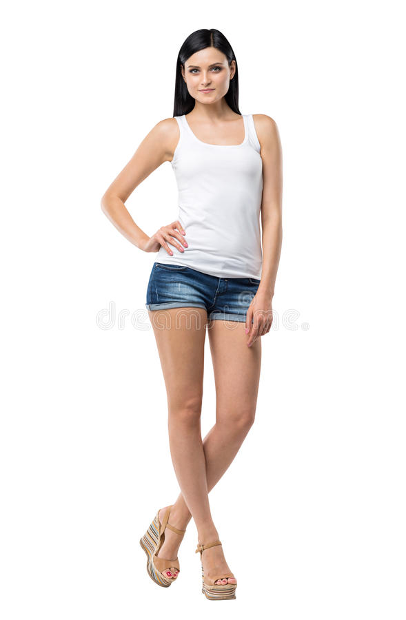 Full length portrait of a brunette woman who is in a white tank top and blue denim shorts. Isolated stock photo