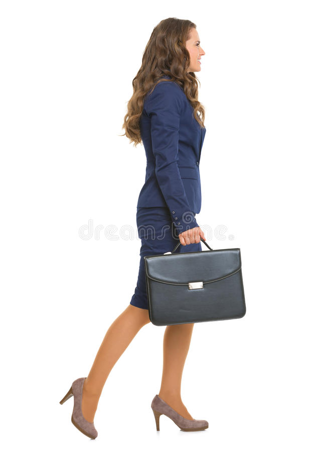 Full length portrait of business woman going sideways. Full length portrait of business woman with briefcase going sideways stock photo
