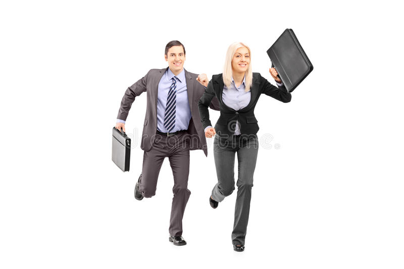 Full length portrait of a businesspeople with briefcases running stock image
