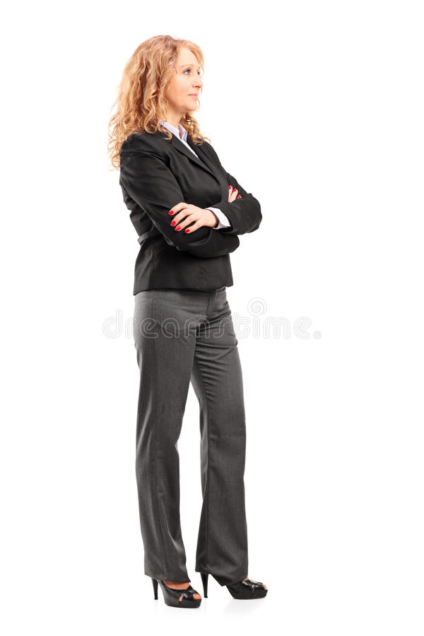 Full length portrait of a businesswoman standing with folded arms. On white background royalty free stock photography