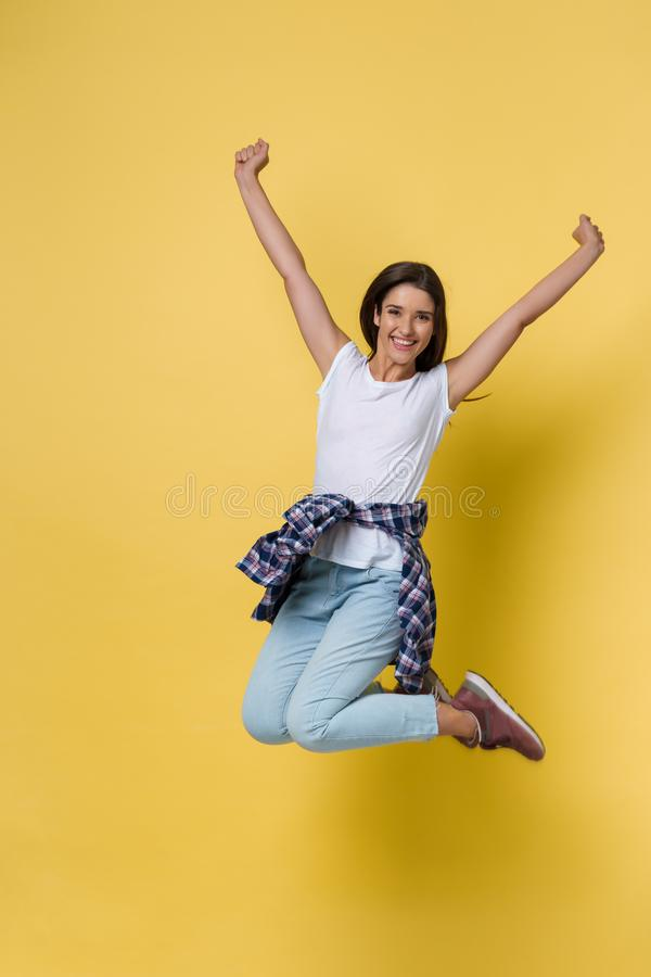 Full-length portrait of carefree girl in white shirt and jean jumping on yellow background. stock image