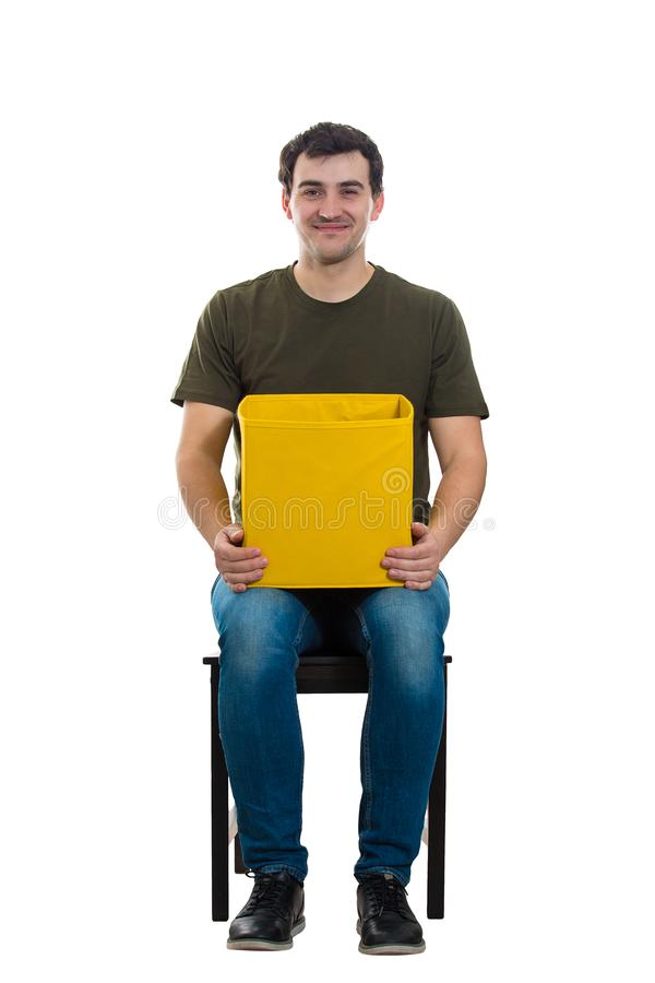 Pleased man holding box. Full length portrait of casual young man seated on a chair looking to camera, with a pleased facial expression as holding a mysterious stock photo