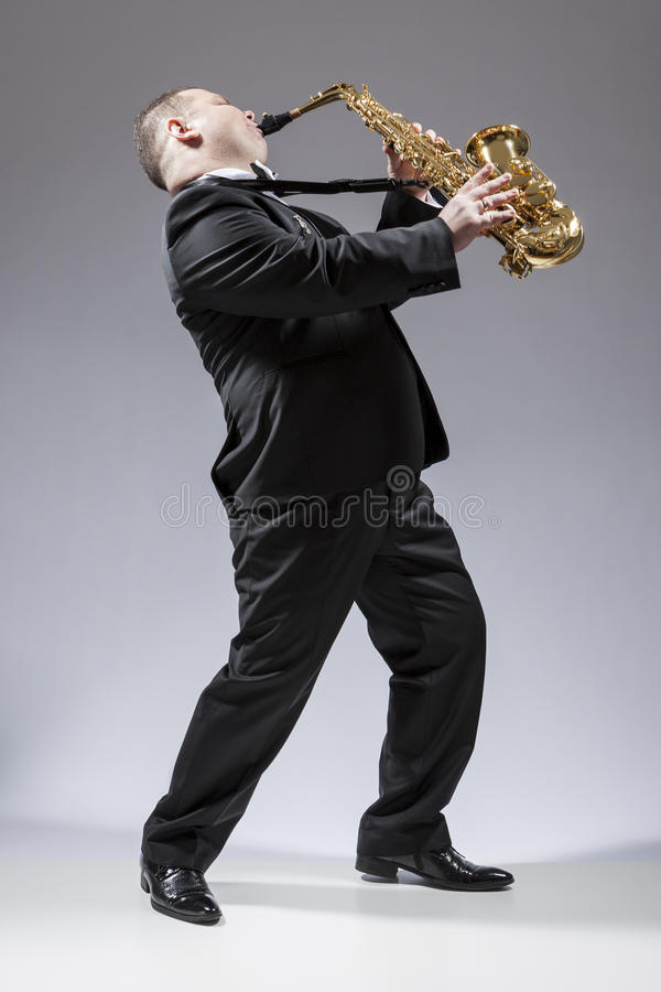 Full Length Portrait of Caucasian Mature Expressive Saxophone Player Playing the Instrument royalty free stock photography