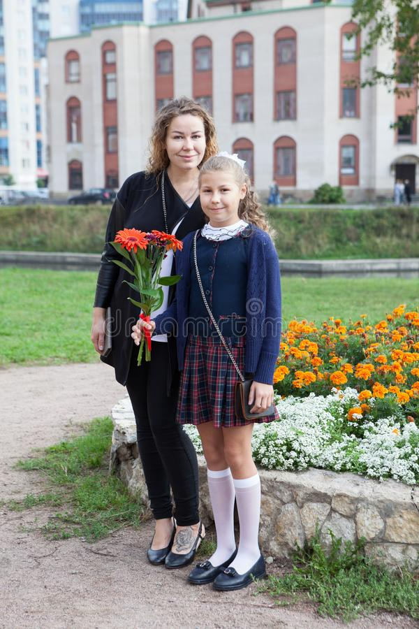 Full-length portrait of Caucasian mother and daughter going back to school together, schoolchild in uniform holding flower stock photography