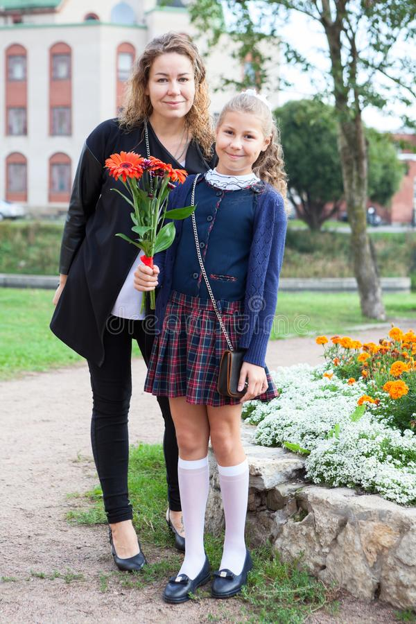Full length portrait of Caucasian mother and schoolgirl in uniform going back to school, daughter holding flower stock photos