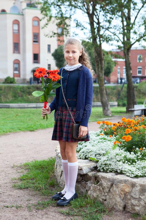 Full-length portrait of Caucasian schoolgirl in uniform going back to school, holding flowers in hand stock photo