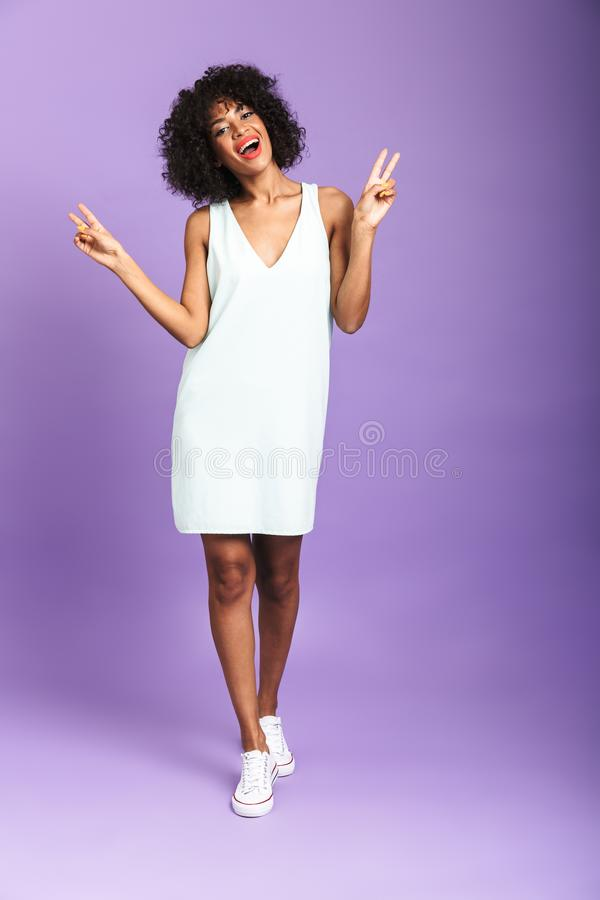 Full length portrait of a cheerful african woman. Wearing dress standing isolated over violet background, posing royalty free stock photography